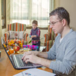 Father working hard in home office with notebook and his boring son playing on the background